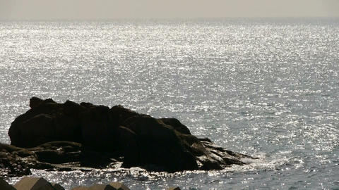 Sparkling water surface and rock reef coastal,horizon,skyline,sunrise,silver Footage