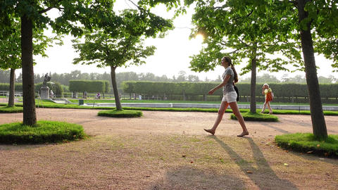 Young slender woman confidently go at formal garden, long slide shot Footage