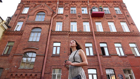 Slender brunette woman turn against brick building, low angle slow motion shot Footage