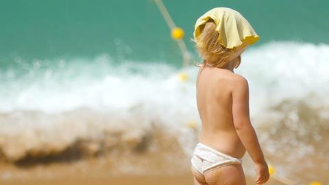 Little girl standing against ocean waves Footage