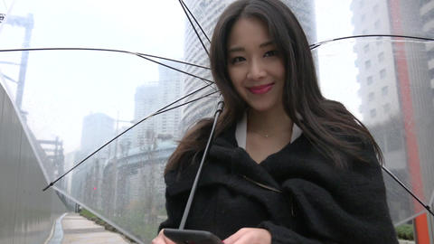 Technology With Asian Woman Texting Using Smartphone In The Rain Live Action