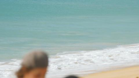 Anonymous people walking on ocean beach Footage