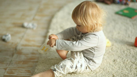 Little blonde girl trying to put socks on Footage