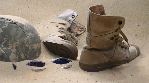 soldier hat boots and sand glass in the desert Footage