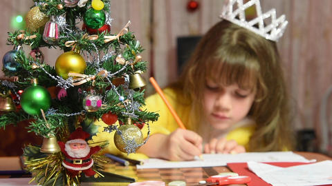 The girl draws at the table Christmas pattern, focusing on the fur-tree in front Footage