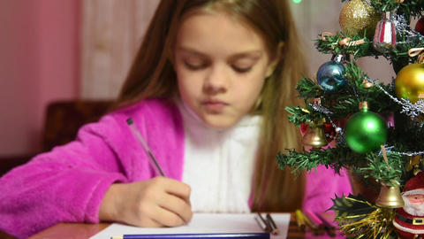 Girl writing a letter to Santa Claus, the focus is on the fur-tree in front of h Footage