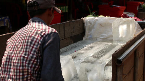 Cambodia man transporting ice block with a hook Footage