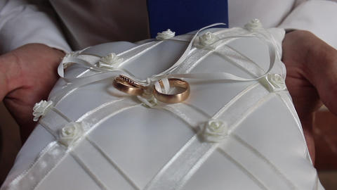 Golden wedding rings with diamonds on a white pillow hand holding and turning Footage