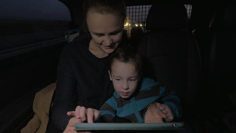 Mother and son playing with touch pad during night car ride ビデオ