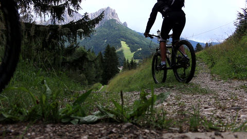 Mountainbiker in the dolomites at Rosengarten mountain passing on a track downhi Footage