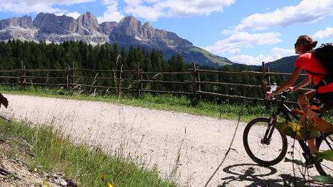 Mountainbiker young couple man and woman riding uphill in sunshine in Italy Footage