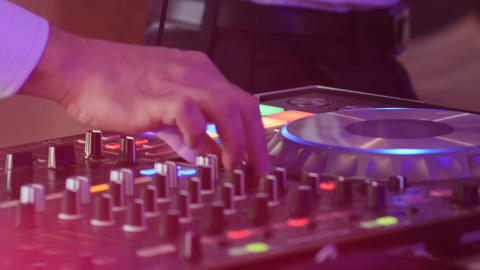 Hands of a DJ who mixes in a mixer during a concert under the limelight colored  Footage