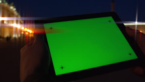 Man uses tablet computer with a green screen on the night street Footage