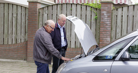 Two Seniors Men Looking Under Hood Of A Car, Europe stock footage