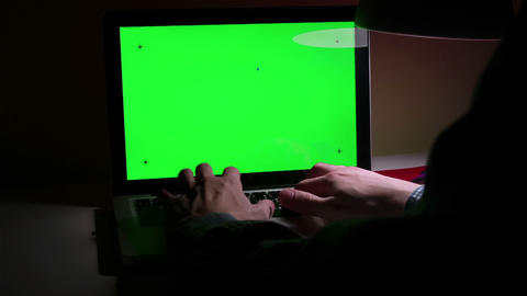 Man use a laptop on his desktop with a green screen Live Action