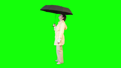 Woman In A Raincoat With An Umbrella On A Green Screen stock footage
