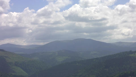 Zoom over mountains with dense forests and fluffy clouds floating above them 04 Footage