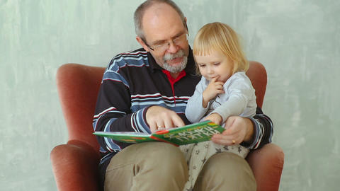 Grandfather read a book to her little granddaughter Footage