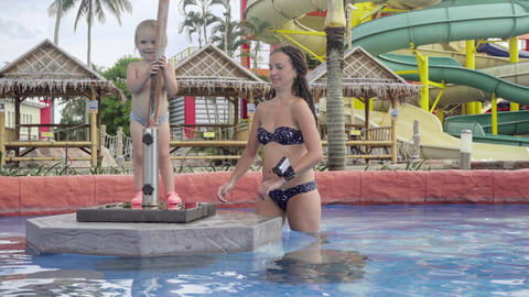 Woman and little girl posing and showing tongues in swimminp pool Footage
