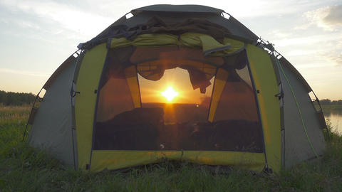Setting sun shines through the camping tent Footage