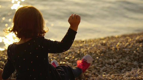 Small girl on the beach throwing stones into the sea Footage