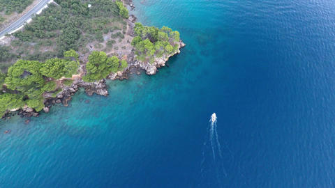 Boat passing near rocky coastline aerial view Footage