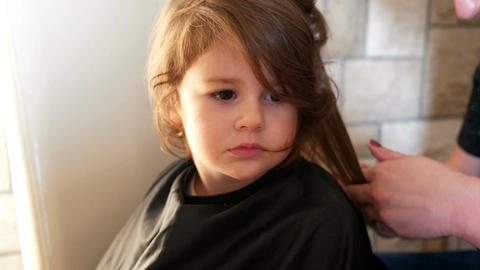 Hairdresser making a hair style to adorable little girl Footage