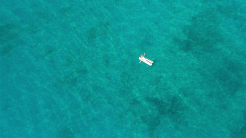 Woman on the beach mattress on the sea aerial view Footage