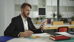 Businessman Looks At Charts And Talking To A Tablet stock footage