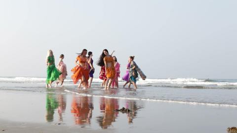 girls in Indian national dresses run out to sand beach dance Footage
