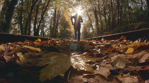 Low Fisheye POV Angle of Man Jogging Down Train Tracks in Fall Season Footage