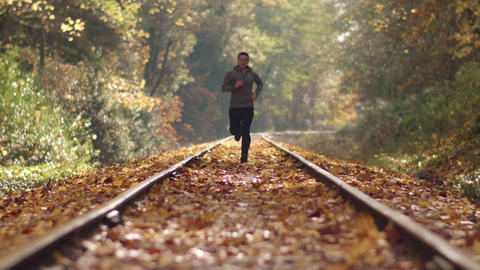Man Jogging Up Train Tracks in Autumn Season with Leaves Falling and Deep Focus Footage