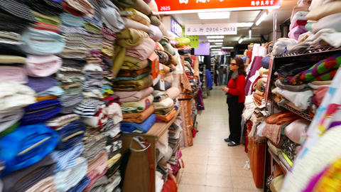 Young visitors and interior of Yongle Fabric Market, walking shot, POV Live Action