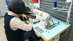 Seamstress sews black cloth using electric stitching machine, tailor at work Footage