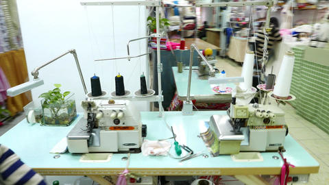 Seamstress lady come from one machine to another overlock Footage