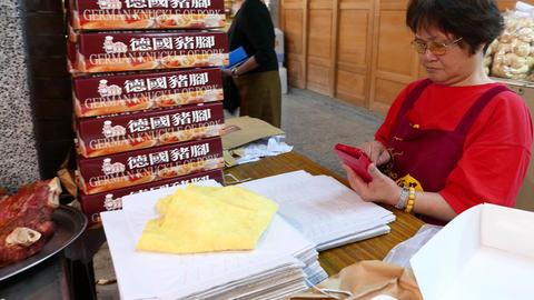 Taiwanese woman computes balance on calculator, market stall Live Action