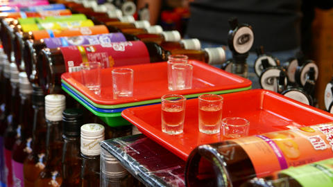 Wine bottles lie in row, test cups on tray, someone take cup to try, close up Live Action