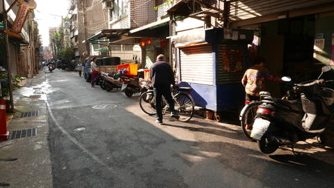 Aged man come and ride bike, scooter traffic on small street, evening sunlight Footage