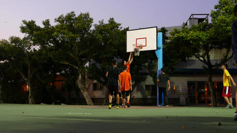 Friends playing basketball game on evening playground. Include sound Footage