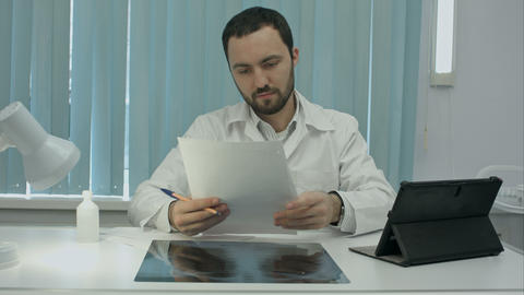 Concentrated male doctor looking at x-ray picture in the medical office Footage