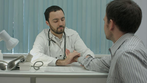 Male bearded doctor in clinicmeasure the pulse of male client Live Action