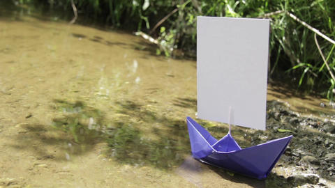 Blue paper boat that ran aground on the sandy shore 243 Footage