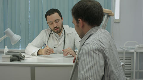 Male bearded doctor in clinic consult sick client with crutches Footage