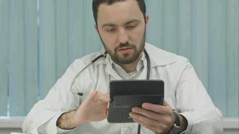 Young male doctor with a calculator make calculations and make notes Footage