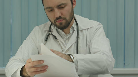 Tired medical doctor tired from paper work with documents Footage