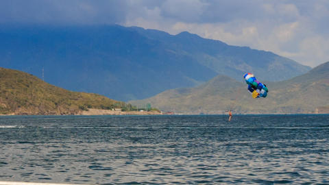 view of parasailing over azure sea against mountains Footage