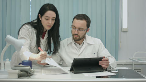Male and female doctors discuss medical document Footage