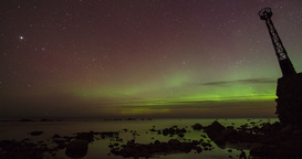 Time lapse pan of Aurora Borealis (Northern Lights) on a rocky seaside