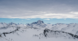 Time lapse of clouds over snow covered alpine mountain range with ski lifts Footage