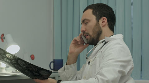 Male doctor talking on cellphone at modern hospital indoors Footage
